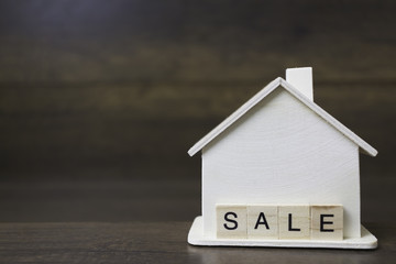House model with sale word on wooden blocks.