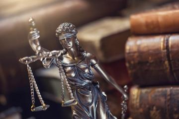 Justizia Figur vor alten Gesetzesbücher