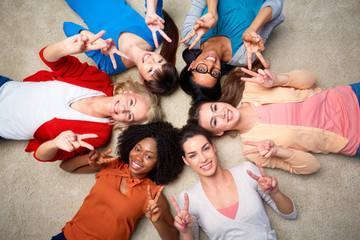 international group of happy women showing peace