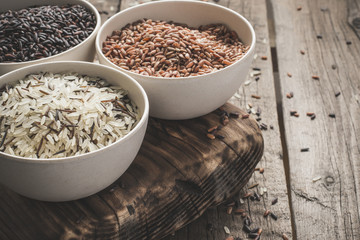 collection of different varieties of rice on wooden rustic background