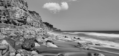 Black and white long exposure landscape with rocky beach in Lagos, Portugal