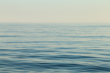 Wall Mural - Calm sea surface. Seascape in early morning hours under clear skies.