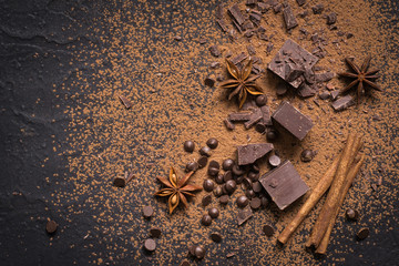 Food dessert background. Pieces of dark chocolate, powder, drops and spices