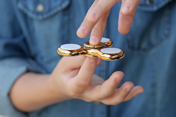 Gold fidget spinner in hand. Popular trendy toy close-up.
