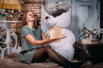 A beautiful sexy girl in a short dress and pantyhose sits on the floor with a big teddy bear in a photo studio