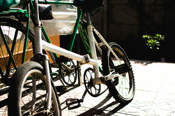 Two old bicycles leaning tagather