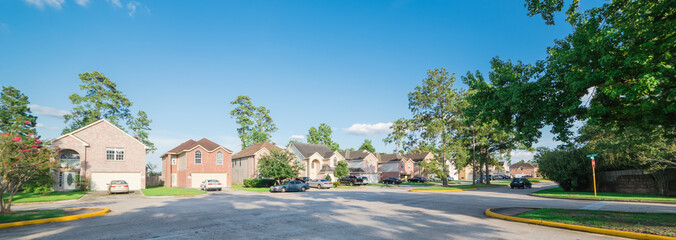 Suburban residential area, row of modern townhomes in Humble, Texas, US. Red brick houses surrounded with tall pine trees, cloud blue sky. Panorama view street intersection and multi-story townhouses.
