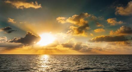 Sunset in the Maldives. Beautiful colorful sunset over the ocean in the Maldives seen from the beach.Amazing sunset and beach in Maldives. Calm water and soft waves. Beautiful maldivian sunbeam.