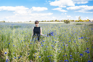Young beautiful girl in a field with cornflowers. A bouquet of beautiful blue flowers