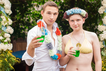 a guy and a girl on a Hawaiian party,