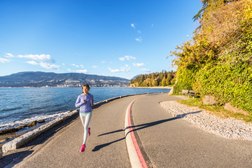 Runner girl running in Stanley Park Vancouver, British Columbia. Woman jogging in city outdoors enjoying healthy active lifestyle. Fotomurales