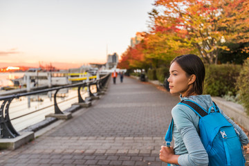 Vancouver city urban lifestyle people at Harbour, British Columbia. Woman tourist with student backpack in city outdoors enjoying autumn season. Fototapete