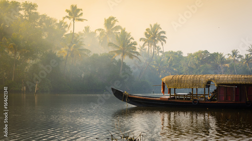 Fototapete A traditional house boat is anchored on the shores of a fishing lake in Kerala's Backwaters, India.