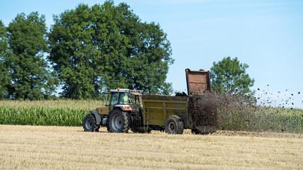 tracteur agricole qui épand le fumier sur le champ Fototapete