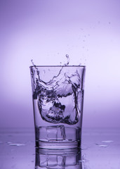 Splash of falling ice in a glass with water