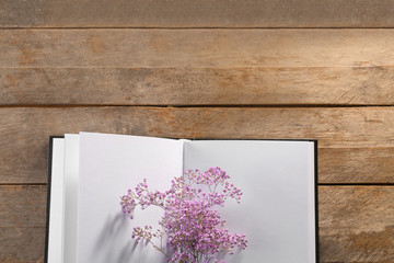 Open book with blank pages and beautiful flowers on wooden background
