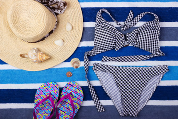 Summer background with straw hat, flip flops and swimsuit. Top view