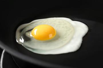 Deurstickers Gebakken Eieren Delicious over easy egg in pan, closeup