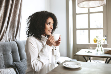 Beautiful African American girl sitting in restaurant with cup in hands. Young pretty lady in white shirt drinking coffee in cafe.Portrait of girl with dark curly hair that thoughtfully looking aside