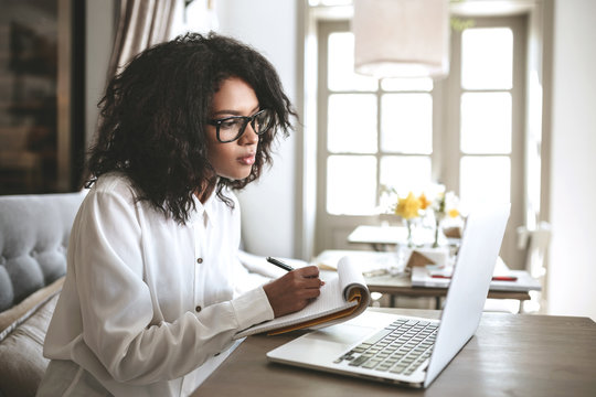 Young African American girl writing notes in restaurant.Nice girl with dark curly hair sitting in cafe with laptop and notebook.Portrait of lady in glasses thoughtfully looking in laptop with notebook