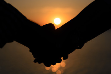 A loving couple (silhouettes of a man and a girl) hold hands in the rays of light at sunset on the sea on a pier.
