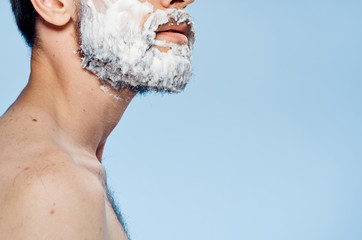 Young guy with a beard on a blue background in shaving foam