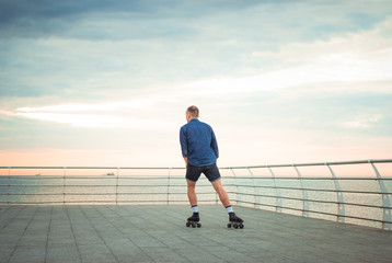 Young caucasian man roller skating with quad skates near the sea