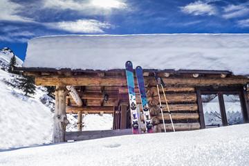 Verschneite Hütte mit Ski in den Alpen