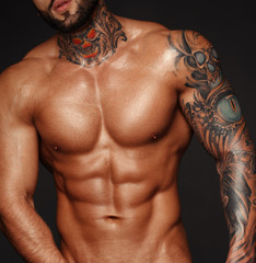 Sexy closeup portrait of handsome topless male model with beautiful eyes. Sexy man or muscular macho, bodybuilder, with muscle torso, body with six packs and abs poses on black background in white