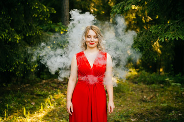 Lonely beautiful young happy blonde girl with curly hair and eyes closed with red lips, red dress with decolette dreaming and breathing in clouds of smoke outdoor on forest background with sunrays.