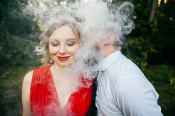 Smoking businessman kissing beautiful young blonde girl with innocent kind face, piercing, eyes closed, red lips, dress with decolette. Clouds of thick smoke. Electronic cigarette. Odd lovers feelings