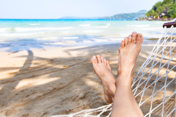 beach holidays background, vacation and relaxation concept, feet of person in hammock