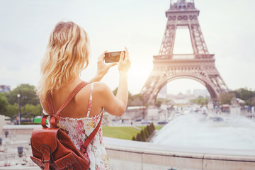 tourist in Paris visiting landmark Eiffel tower, sightseeing in France, woman taking photo on mobile phone Fototapete