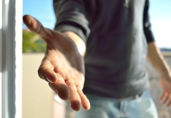 Man raising his hand to the camera to greet. Shake Hands