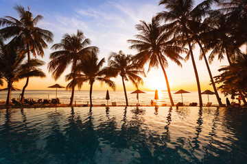 beautiful sunset on the beach, holidays background, reflection of silhouettes of palm trees in swimming pool of hotel