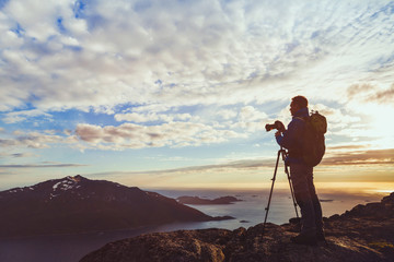 photographer with tripod taking panorama of beautiful nature landscape in Norway at sunset, silhouette of man with camera in fjords