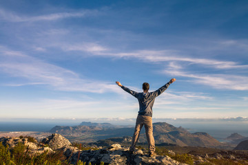 man standing with raised hands on top of Table mountain in Cape Town, South Africa