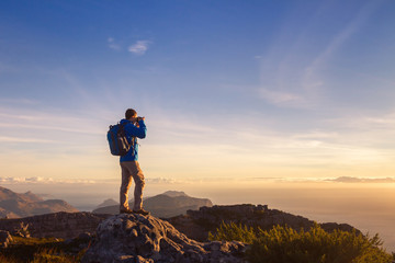 nature photographer traveler taking photo of beautiful landscape from top of the mountain