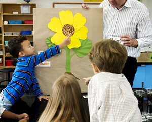 Diverse group of kindergarten students learning flower structure in science class