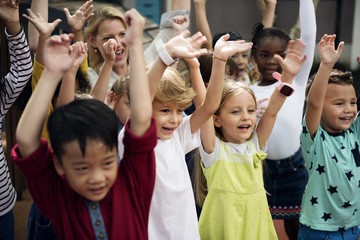 Group of diverse kindergarten students with arms raised