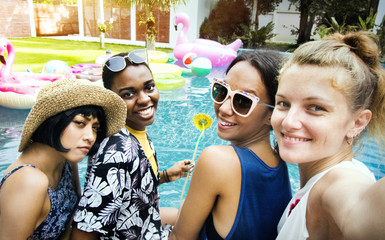 Group of diverse women taking selfie by the pool