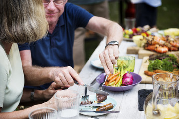 Man sharing food to woman at backyard barbecue party