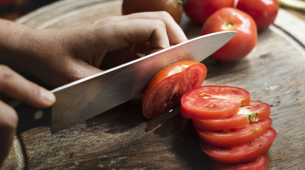 Hands holding a knife slicing a tomato