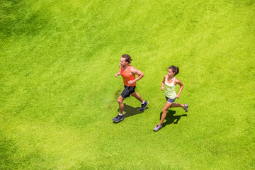 Runners running healthy people lifestyle. Active couple jogging together on grass park view from above. Summer weight loss training program.
