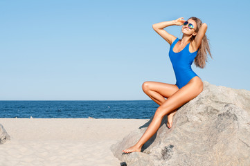 Sexy tanned woman in blue one-piece swimsuit on the tropic beach