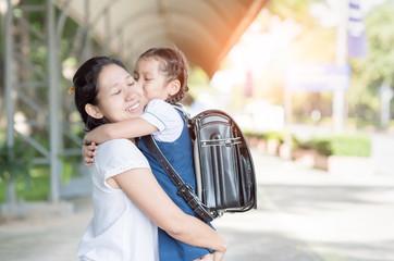 mother hug and kiss cute girl student