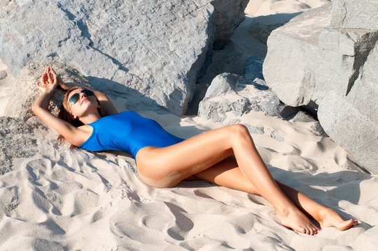 Woman lying on sand in blue one-piece swimsuit on the beach