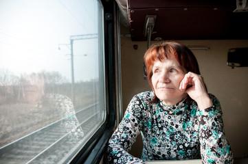 Elderly woman in a train looks out the window