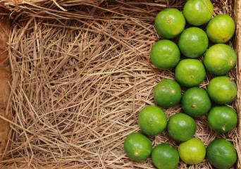 Fresh lime in wood  tray with  straw background.