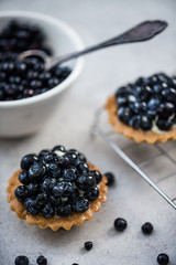 Filling blueberry tart with fresh fruits